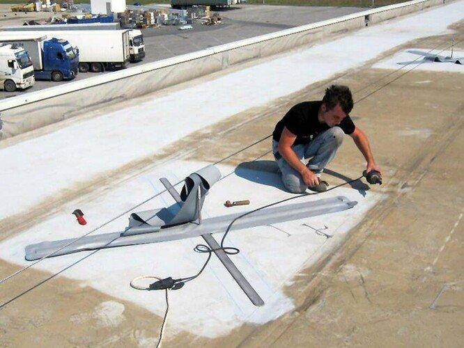 Foto van een installateur die het ABS-Lock OnTop aanlijnpunt monteert zonder het dak te doordringen.