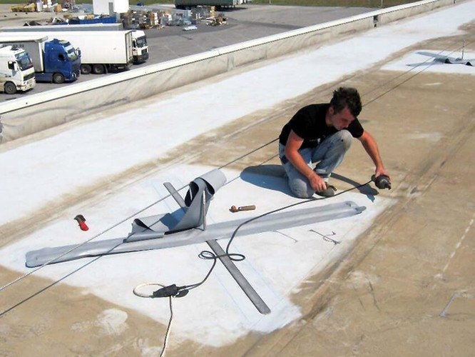 Photo showing a technician installing an ABS-Lock OnTop anchor without penetrating the roof surface