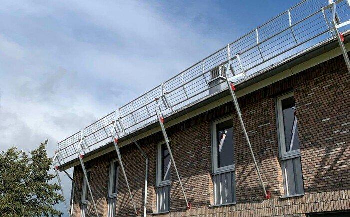 Een eenvoudig te transporteren dakrandbeveiligng in gebruik op een hellend dak.