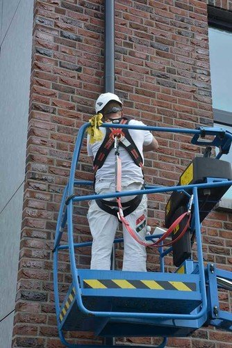 Photo showing a worker carrying out maintenance work on a rain pipe who has hooked up his safety harness for added fall protection