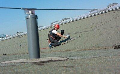 Arbeiter kontrolliert Systemschild auf einem Flachdach
