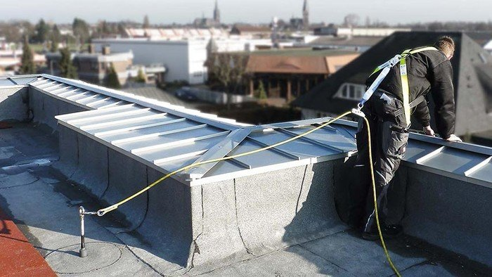 Image showing a worker at the edge of a roof who has hooked up to an ABS-Lock III-BE anchor