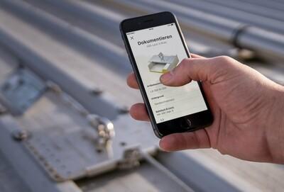 Foto eines Smartphones mit offener Doku-App von ABS Safety
