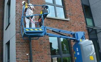 Een medewerker met persoonlijke valbeveiliging aan het werk op een hoogwerker.