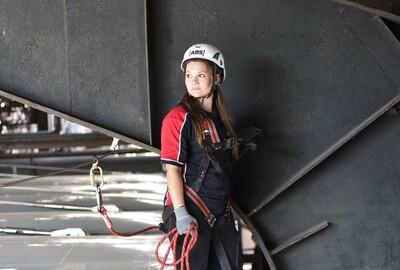 Das Bild zeigt eine junge Frau, die eine persönliche Schutzausrüstung gegen Absturz trägt.