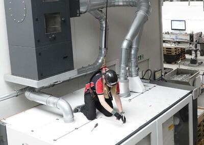 Das Bild zeigt eine gegen Absturz gesicherte Höhenarbeiterin auf einer Maschine
