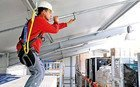 Photo showing an industrial worker who has hooked up to a mobile anchor attached to a steel girder to protect himself from falling