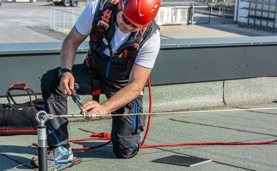 Image showing a worker using fall arrest equipment whilst carrying out maintenance on a lifeline system installed on a flat roof surface