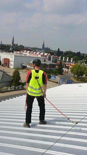Foto von einem gegen Absturz angeleinten Dacharbeiters, der eine Warnweste mit integriertem Auffanggurt trägt.