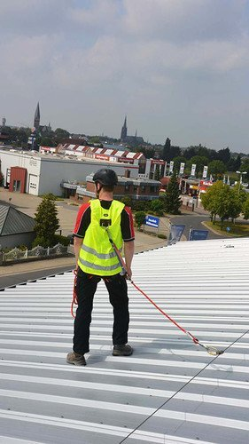 Photo showing a roof worker wearing a high-viz ABS ComfortVest and integrated safety harness hooked up to fall arrest system