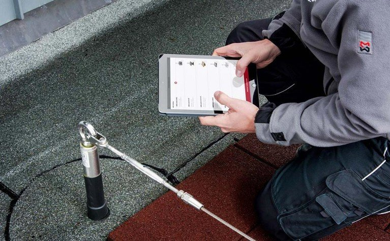 Image showing a worker documenting a fall arrest system on a tablet