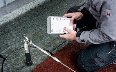 Arbeiter dokumentiert eine Absturzsicherung auf einem Tablet