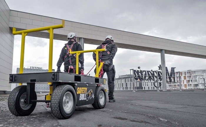 Image showing two workers pulling a temporary ABS SafetyBull anchorage system along behind them on a flat roof surface.