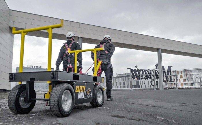 De tijdelijke aanlijnvoorziening wordt door twee medewerkers op een plat dak getrokken.