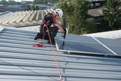 Foto eines Dacharbeiters, der sich zum Schutz gegen einen Absturz angeleint hat.