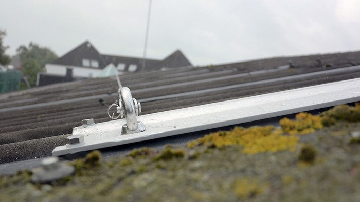 Photo showing an ABS-Lock Wave 60 anchorage point slotted to the waves of a corrugated roof surface