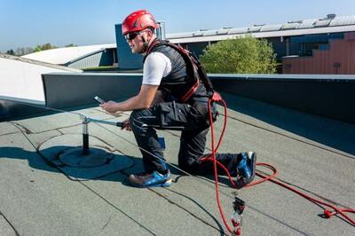 Foto eines Monteurs auf dem Dach, der mit dem Handy die vorgeschriebene Wartung einer Absturzsicherung dokumentiert.