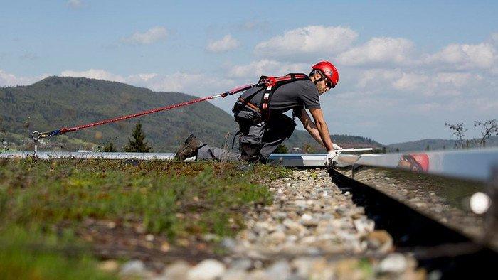 Einsatzfoto eines am Sekuranten angeleinten Höhenarbeiters auf dem Flachdach.