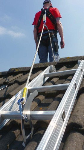 The image shows a roof safety hook with a roofer's ladder hooked onto it. The roofer is also safely hooked up