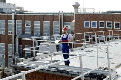 Das Bild zeigt einen Arbeiter auf einem Dach, dessen Absturzkanten mit einem Schutzgeländer gesichert sind.