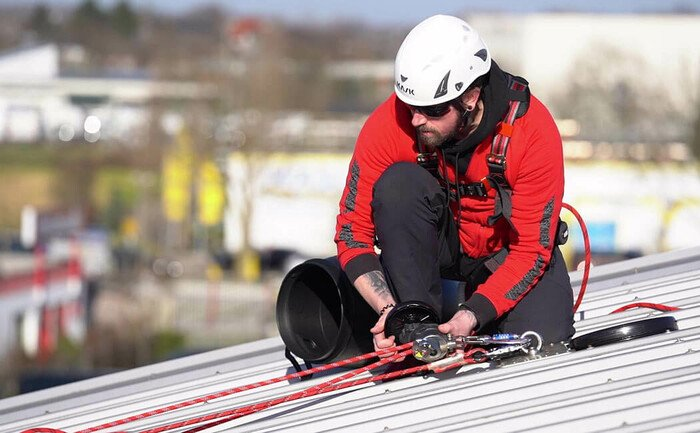 Ein Arbeiter auf einem Steildach bedient die Handkurbel des ABS Rettungsgerät MRG9 Easy
