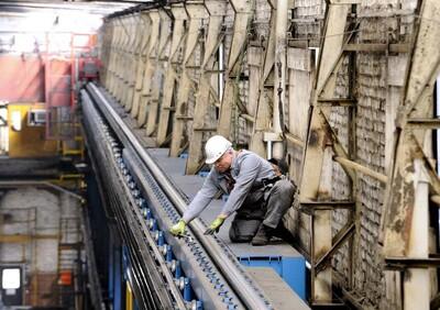 Das Bild zeigt einen Industrie-Arbeiter, der mit einem Seilsystem gegen einen Sturz von der viele Meter hohen Kranbahn gesichert ist, auf der er gerade arbeitet.