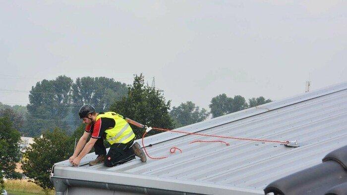 Foto eines Dachdeckers an der Dachkante, dessen reflektierender Auffanggurt mit einem Anschlagpunkt verbunden ist.