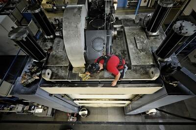 Das Bild zeigt einen Arbeiter, der mit einem Anseilschutz gegen einen Sturz von der hohen Maschine gesichert ist, auf der er steht.