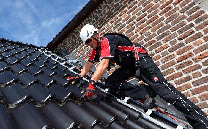 Dachdecker auf einem Steildach gesichert an einem ABS Dachhaken
