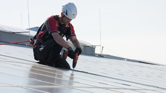 Image showing a worker on a photovoltaic system - hooked up to the anchor to protect himself from falling