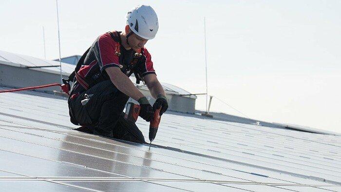 Das Bild zeigt einen Arbeiter an einer Photovoltaikanlage, der sich zur Absturzsicherung an einem Sekuranten angeleint hat.