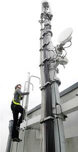 Een monteur die op een vaste ladder beveiligd is tegen vallen.