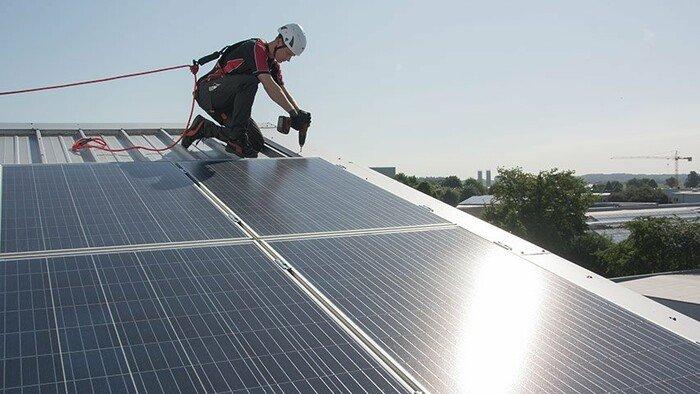 Einsatzfoto eines PV-Technikers auf dem Steildach, der einen Schutzhelm mit Kinnriemen trägt.