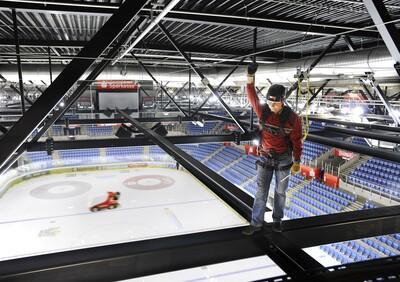 Das Bild zeigt einen Rigger, der sich gegen Absturz gesichert in den Traversen einer Veranstaltungshalle bewegt