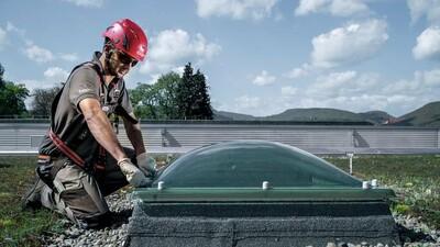 Das Bild zeigt einen sicher angeleinten Höhenarbeiter bei der Lichtkuppel-Reinigung auf dem Flachdach.