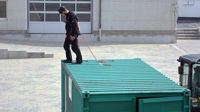Vue d'un travailleur se tenant au sommet d'un container, attaché à un ABS-lock X-Flat
