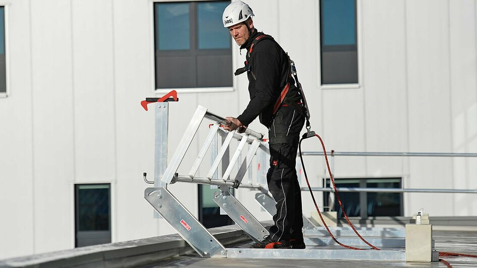 Image showing a roof worker unfolding an ABS Mobile Guard - flat guard rail
