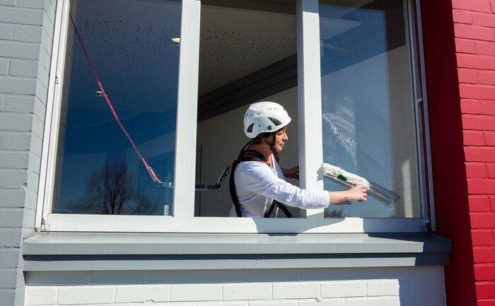 L'illustration montre une femme arrimée nettoyant une fenêtre et se penchant vers l'extérieur.