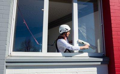 Das Bild zeigt eine angeleinte Frau, die ein Fenster reinigt und sich dazu hinauslehnt.