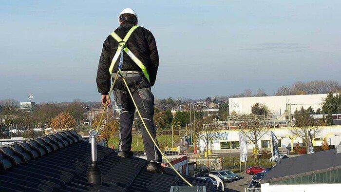 Foto eines Höhenarbeiters auf einem geneigten Dach, dessen PSAgA am Sekuranten befestigt ist.