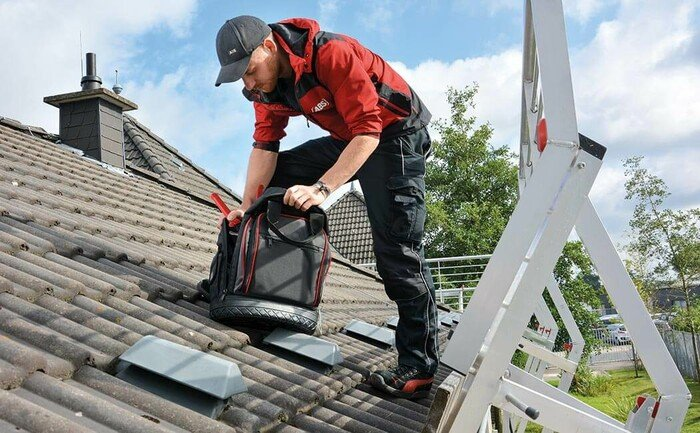 Image showing a technician installing a lifeline system to protect workers from falling off a roof surface