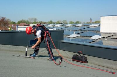 Das Bild zeigt einen gegen Absturz gesicherten Mann auf dem Dach, der eine Manschette zur Abdichtung des Anschlagpunktes montiert hat