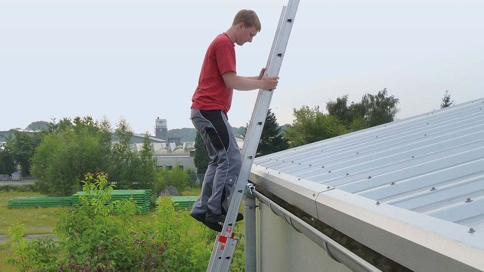 Image showing a roofer at the top of a secured ladder climbing onto the roof