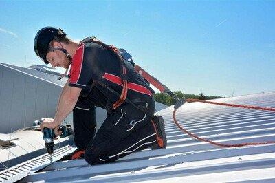 Mit PSAgA angeleinter Dacharbeiter auf Metalldach.
