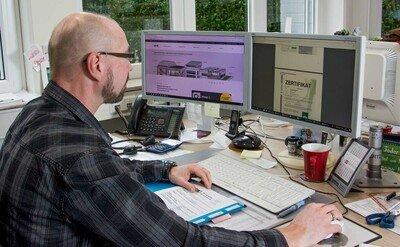 Mitarbeiter sitzt im Büro am PC und arbeitet mit ABS-Lock Book