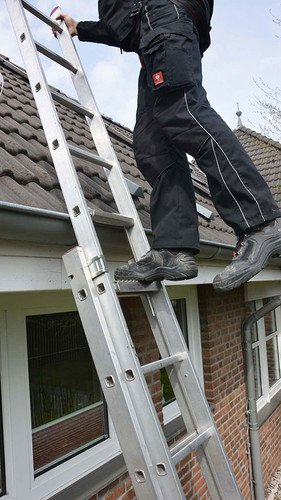 Image showing a roofer climbing onto a pitched roof surface from a ladder secured using an ABS LaddQuick device