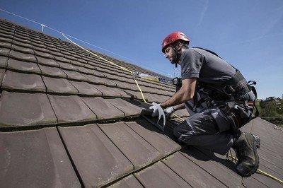 Das Bild zeigt einen zum Fallschutz angeleinten Dachdecker bei der Arbeit