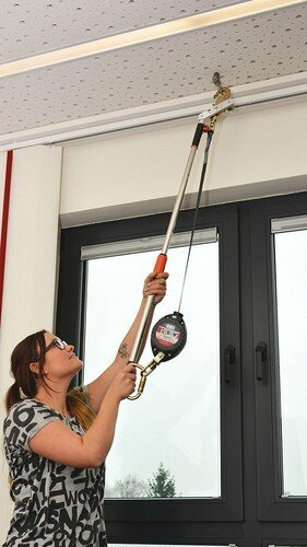 Image showing a young woman using an ABS UP System to hook up her PPE equipment