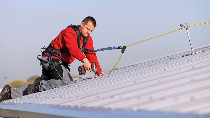 Image showing an installation technician working on a sandwich roof surface who has connected up to an anchor to protect himself from falling