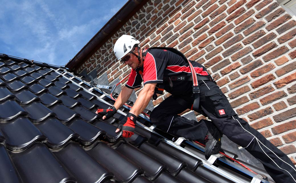 Roofer on a pitched roof surface - secured using an ABS roof safety hook
